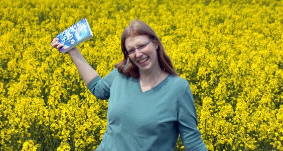 """Foto von Laura Kier mit dem Buch """"Der Geist der Spiegelkatze"""" in der Hand in einem Rapsfeld"""