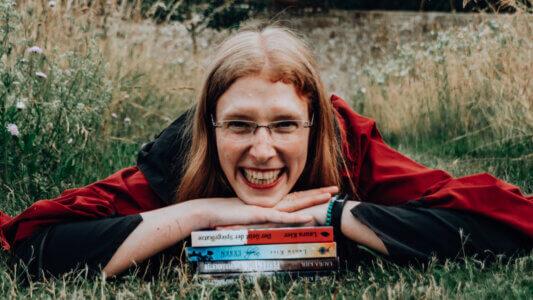 Laura Kier mit ihren veröffentlichten Büchern im Gras auf dem Boden liegend